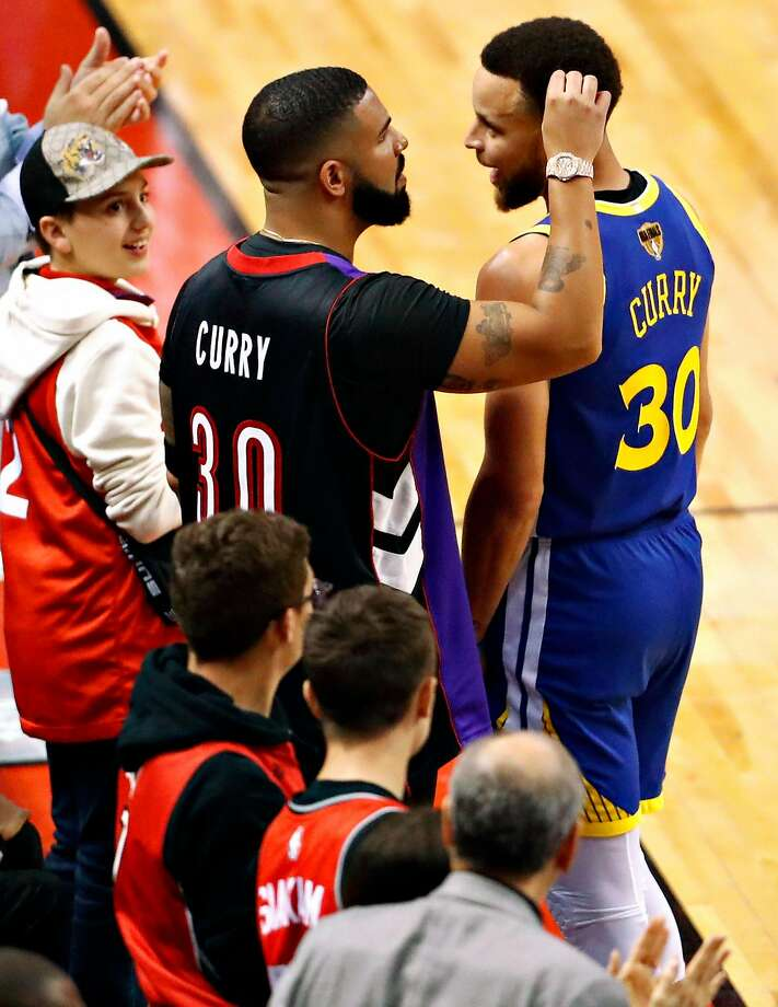 Drake and Golden State Warriors' Stephen Curry exchange pleasantries during Toronto Raptors' 118-109 win in NBA Finals' Game 1 at ScotiaBank Arena in Toronto, Ontario, Canada, on Thursday, May 30, 2019. Photo: Scott Strazzante / The Chronicle