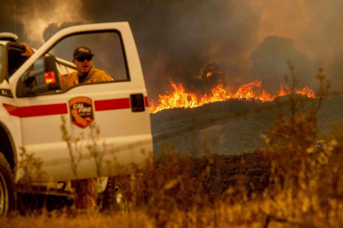 The Ranch Fire, part of the Mendocino Complex Fire, crests a ridge as Battalion Chief Matt Sully directs firefighting operations on High Valley Rd. near Clearlake Oaks, California, on Sunday, Aug. 5, 2018. / AFP PHOTO / NOAH BERGERNOAH BERGER/AFP/Getty Images