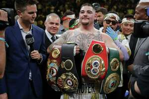 Andy Ruiz poses with championship belts Saturday after defeating Anthony Joshua to capture the unified world heavyweight title. Ruiz has become a folk hero overnight among people of Mexican ancestry in the United States.