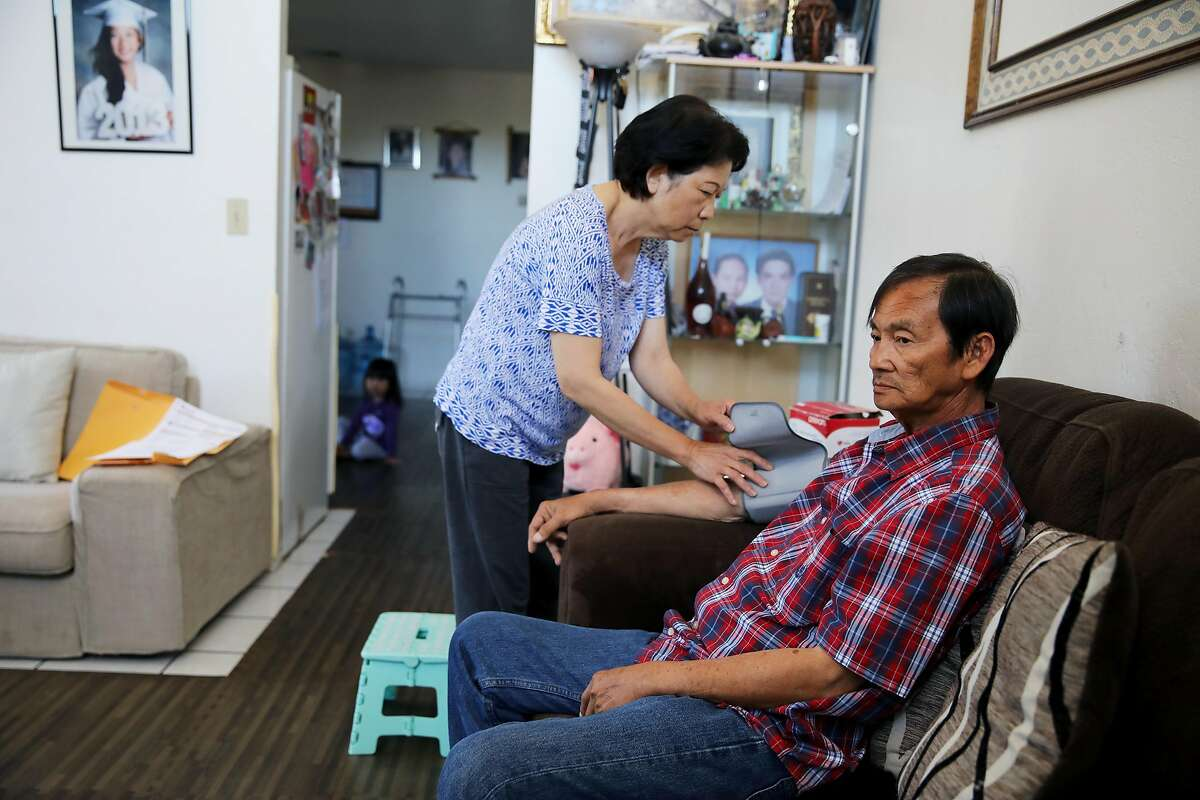 Melody Bui, 61, checks Tu Le's, 63, blood pressure in their home in San Jose, Calif., on Thursday, June 6, 2019. Bui is her husband's full-time caretaker as he battles cancer. Le's Vietnamese brothers, Lam Le and Hiep Nguyen, are desperate to travel to the United States to donate bone marrow to their dying sibling. The brothers applied for temporary visitor visas in late May, but were denied entry to the U.S. just a few days later, the family said. A bone marrow transplant is the only thing that can save the 63-year-old man.