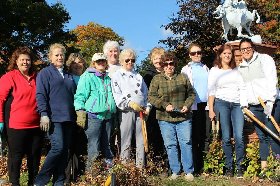The Olde Ripton Garden Club stands with volunteers from Gexpro who are part of a Community Outreach Program while cleaning up the Huntington Green. - Aaron Berkowitz photo