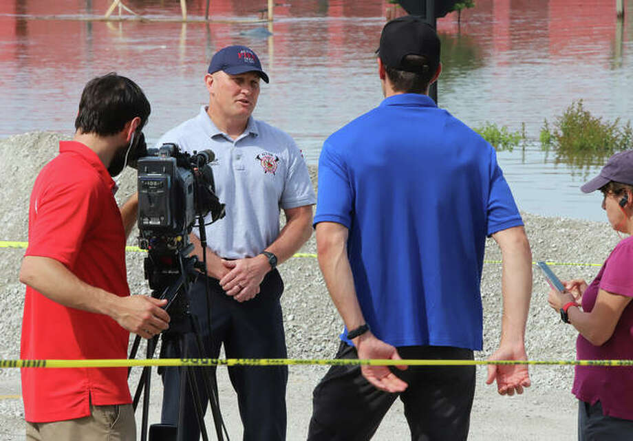 Alton Fire Chief Bernie Sebold gives an interview to a crew from The Weather Channel documenting the flooding in Alton.