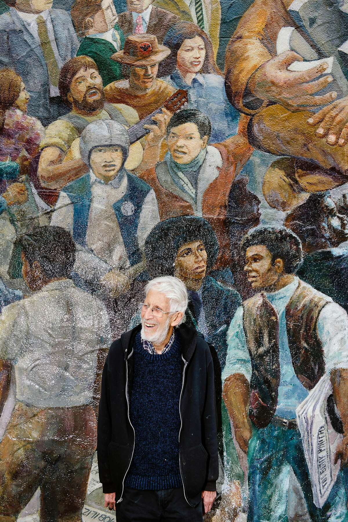 Osha Neumann, a Berkeley lawyer, advocate and artist, stands for a portrait in front of the People History of Telegraph Avenue mural that he designed and worked on in the 1970's, in Berkeley, Calif, on Monday, May 20, 2019.