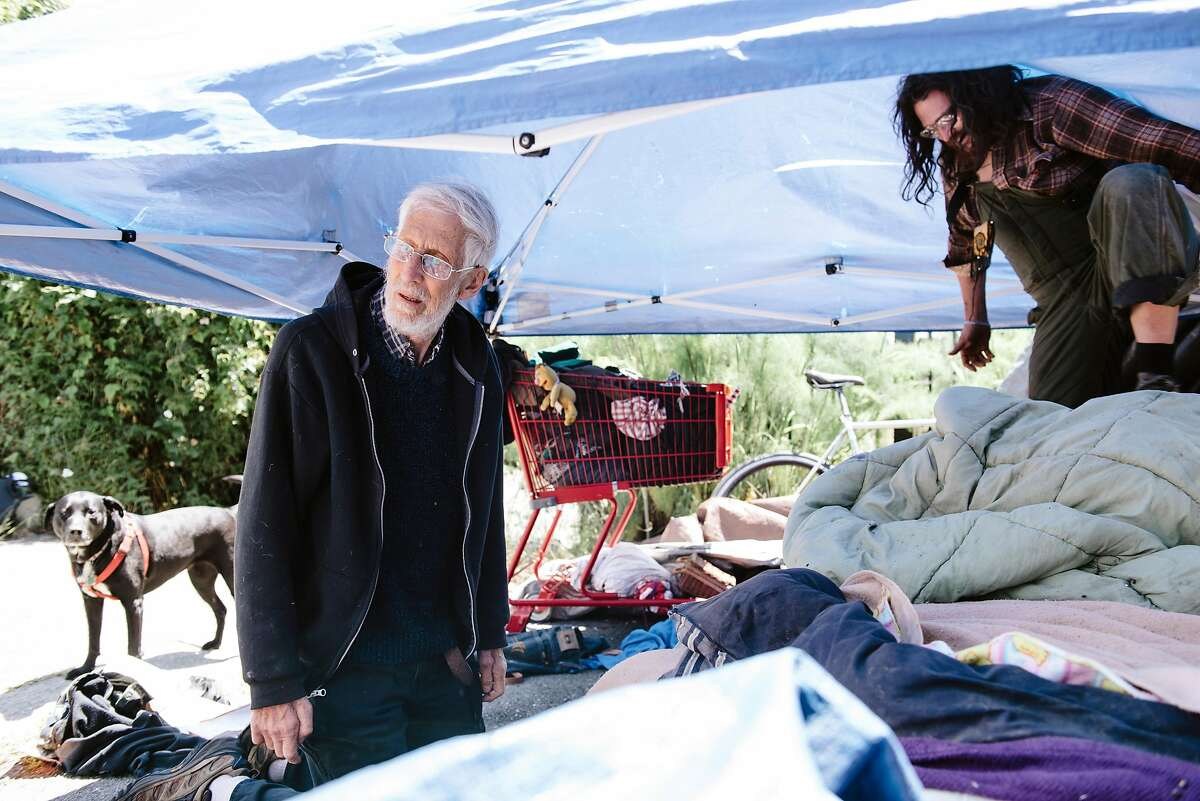 Osha Neumann, left, a Berkeley lawyer, advocate and artist, visits with some homeless folks, including Jake Clakley, at their encampment in Berkeley, Calif, on Monday, May 20, 2019.