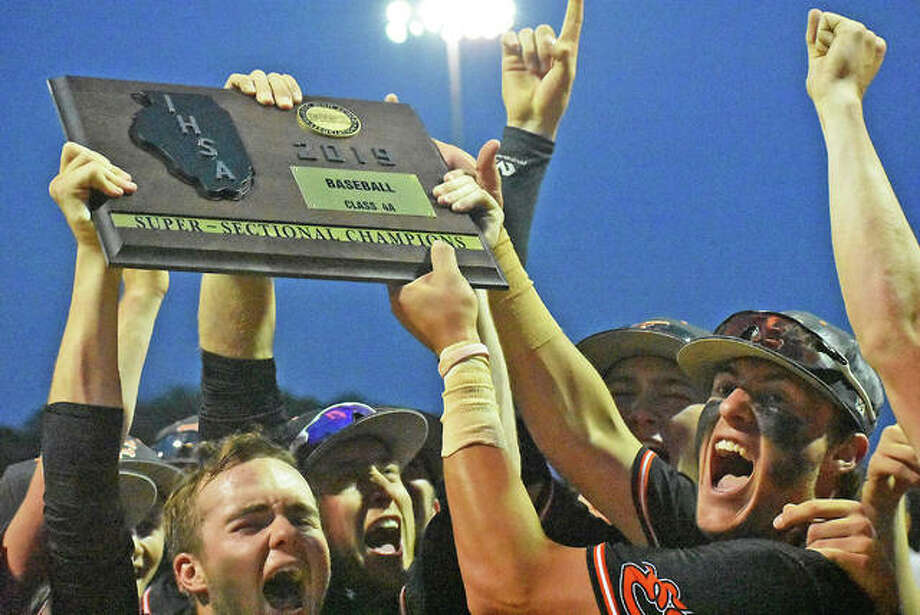 The Edwardsville Tigers baseball team celebrates with its Class 4A super-sectional plague Monday in Bloomington. The Tigers will play in the state finals in Joliet on Friday and Saturday. Photo: Matt Kamp / Hearst Illinois