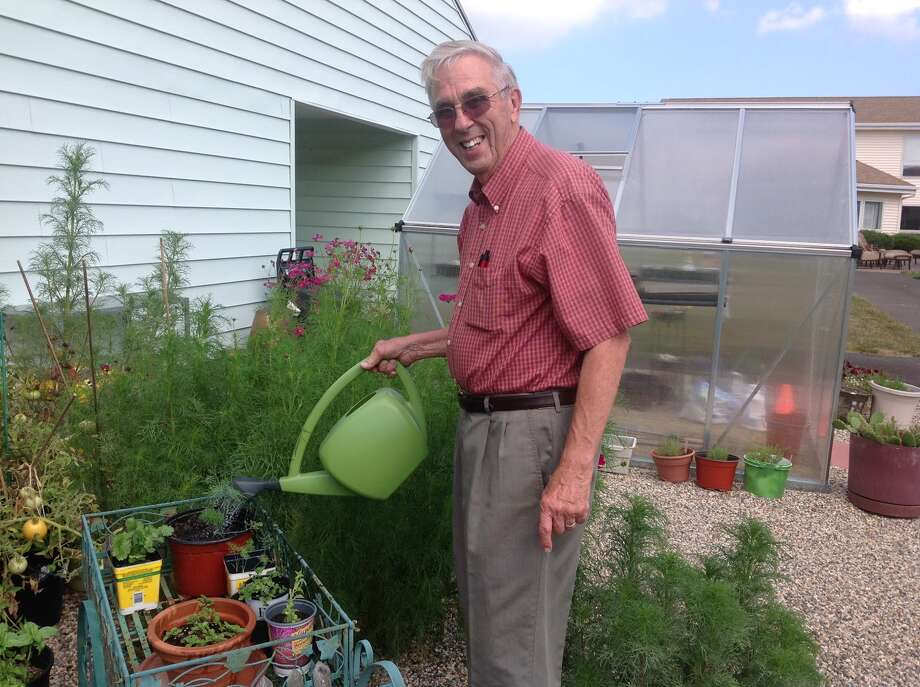 Douglas Osgood watering the garden he had put into The Wesley Village Campus