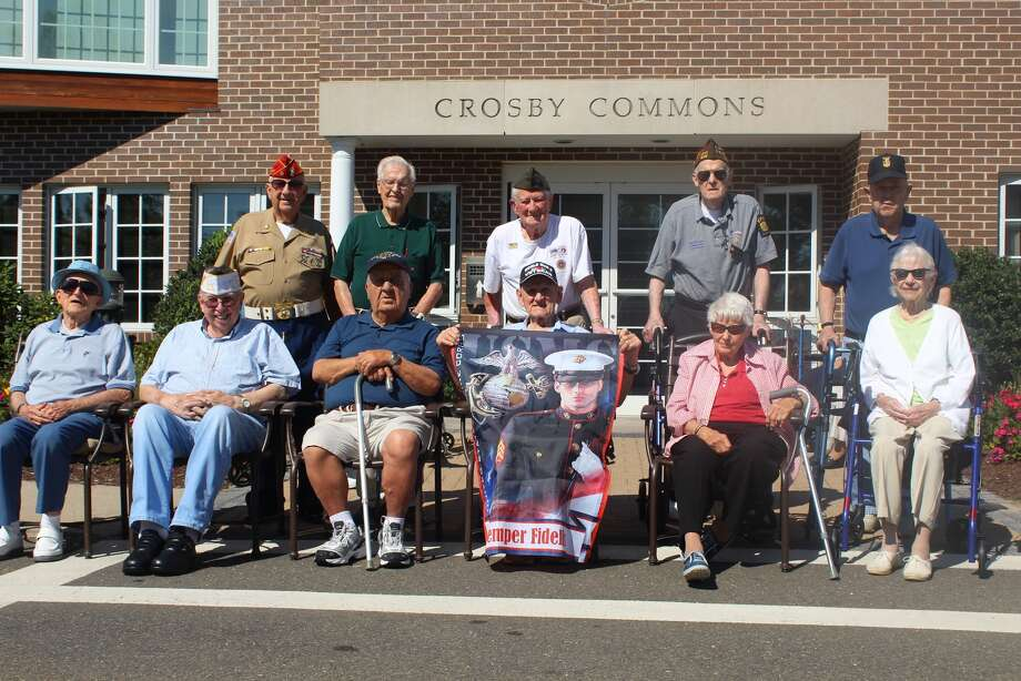 All of the residents who are veterans at Wesley Village's Crosby Commons section community celebrated a Flag Dedication Ceremony in front of their main building (Aaron Berkowitz photo)
