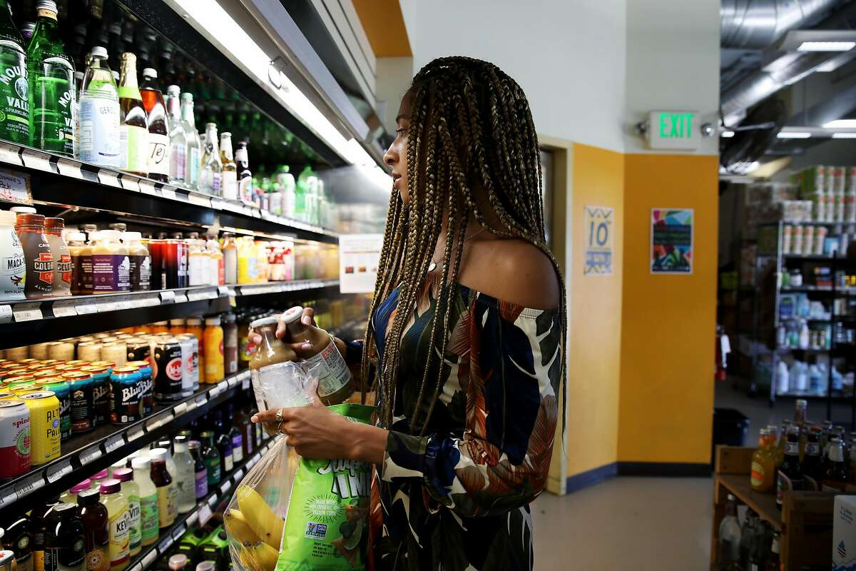 Jasmine Curtis shops at the Mandela Grocery Cooperative, located at 1430 7th St. in Oakland, Calif., on Tuesday, June 4, 2019. Curtis, founder and CEO of Avocurl, a natural hair care business, sells her products at the store. The grocery store is celebrating its 10th anniversary with a block party in West Oakland as the city's only cooperative grocery on Friday from 3-8 p.m. It's also in the process of organizing a sister market in East Oakland in collaboration with the urban farming nonprofit Acta Non Verba.