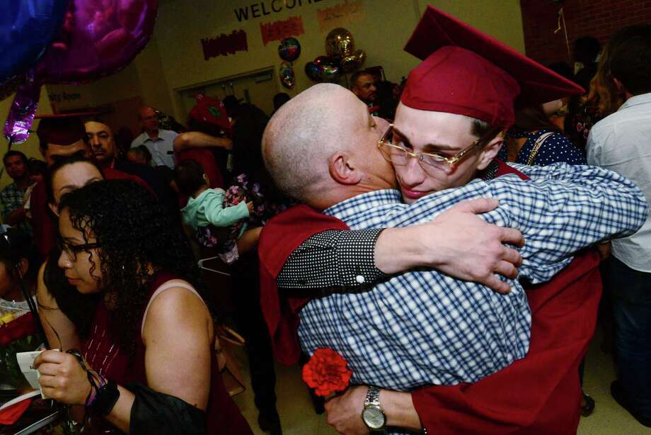 AJ Toscano receives a congratulatory hug from his father following the Norwalk Adult Education High School Graduation Class of 2019 ceremonies on Wednesday, at the Center for Global Studies at Brien McMahon High School in Norwalk. The event was Norwalk's final Adult Education graduation before its merger with Stamford's program. Photo: Erik Trautmann / Hearst Connecticut Media / Norwalk Hour