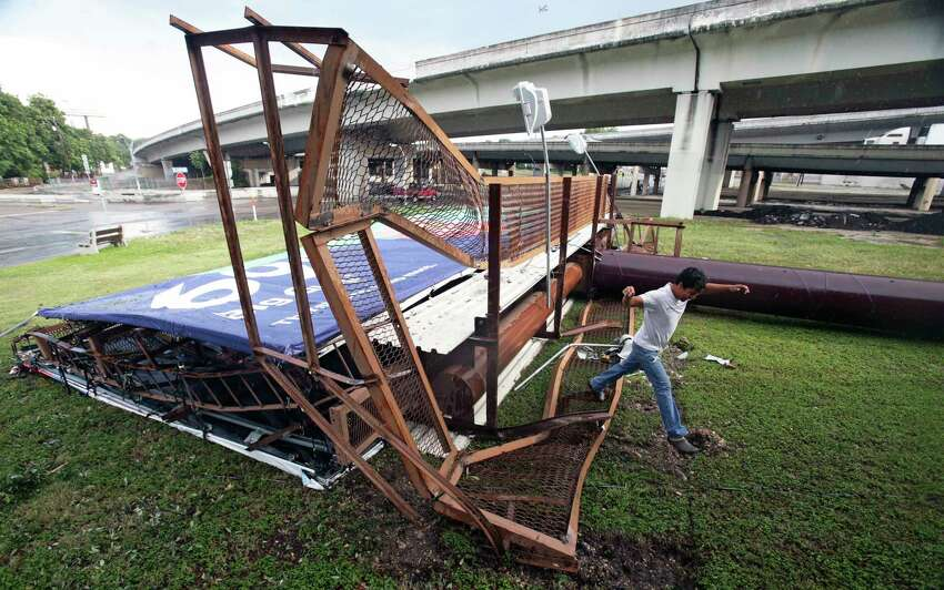 As rain begins to fall again a bystander scampers off a large road sign on I10 near downtown which had been pushed over by high winds as a rainstorm downs trees, kills power supply and clogs the roadways with high water Thursday afternoon in San antonio on June 6, 2019.