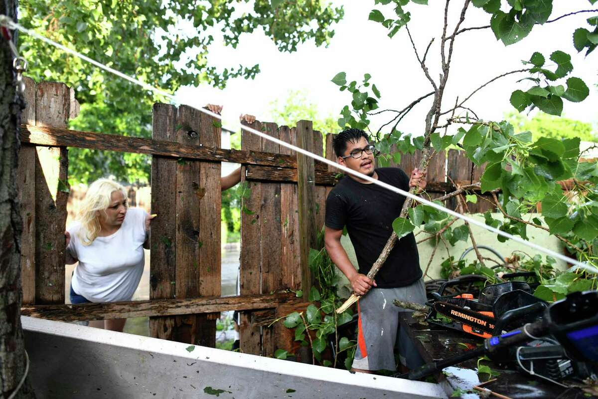 Jarrod Ramoz pulls downed branches from his yard as Cindy Mireles helps hold up a fence that was knocked down on Catalina Avenue near West Ridgewood Court by sudden wet weather in San Antonio on June 6, 2019.