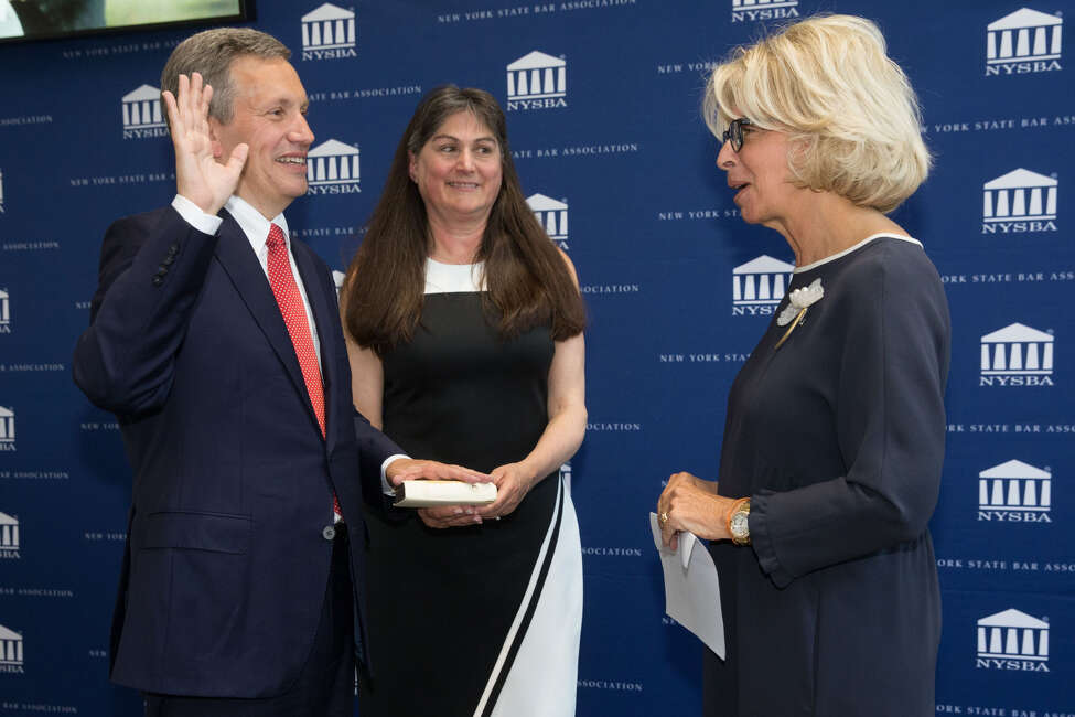 """Henry M """"Hank"""" Greenberg takes the oath as leader of the New York State Bar Association Thursday June 6, 2019, from Chief Judge Janet DiFiore. Greenberg's wife Hope Engel is at center."""