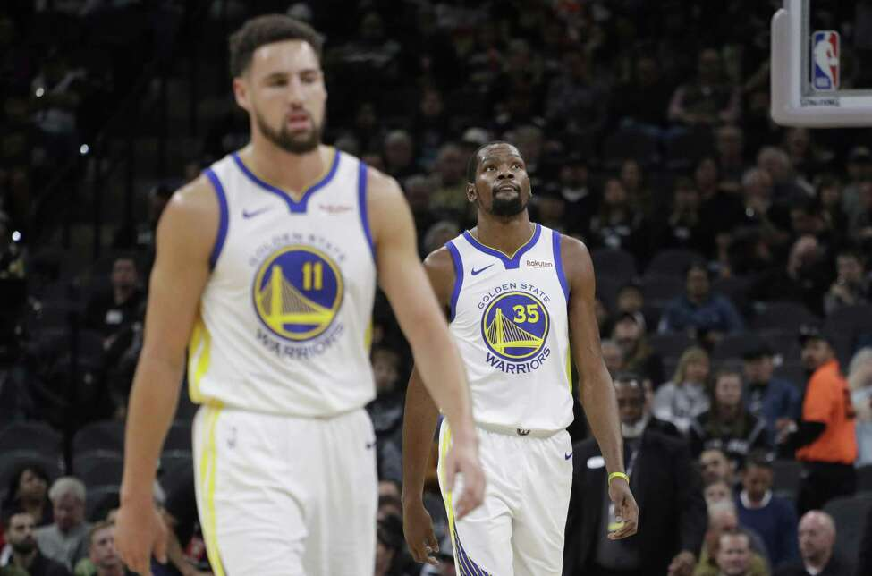 Golden State Warriors forward Kevin Durant (35) and guard Klay Thompson (11) walk off the court during a timeout during the first half of an NBA basketball game San Antonio Spurs, Sunday, Nov. 18, 2018, in San Antonio.