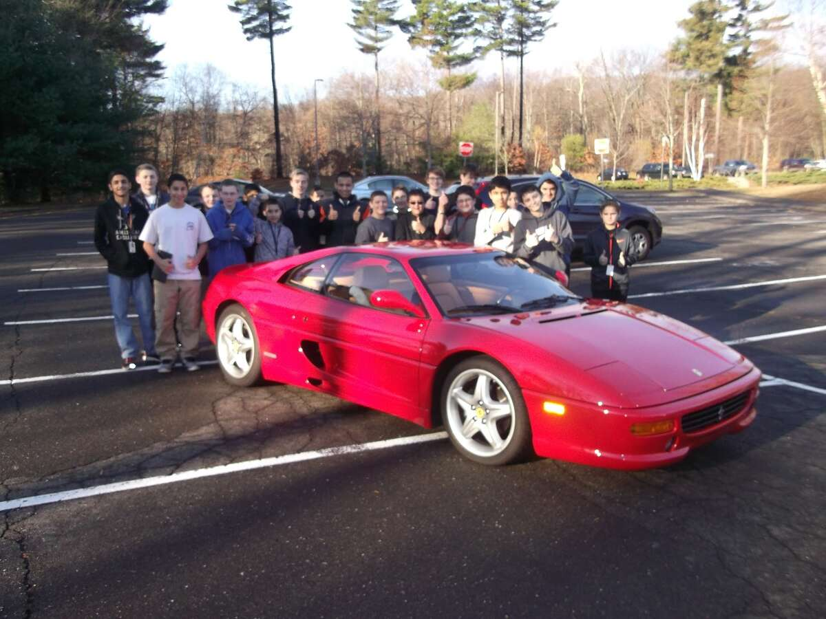 Club members gathered for their traditional pose as they do with each car they look at.