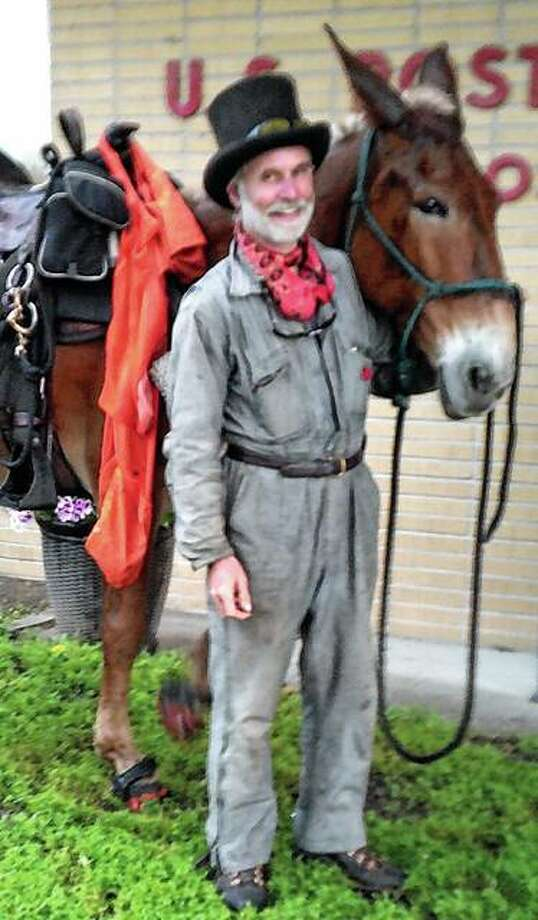Bernie Harberts stands with his traveling companion, a 12-year-old mule named Cracker, outside the Meredosia post office. Photo: Shirley Bilyeu | For The Journal-Courier