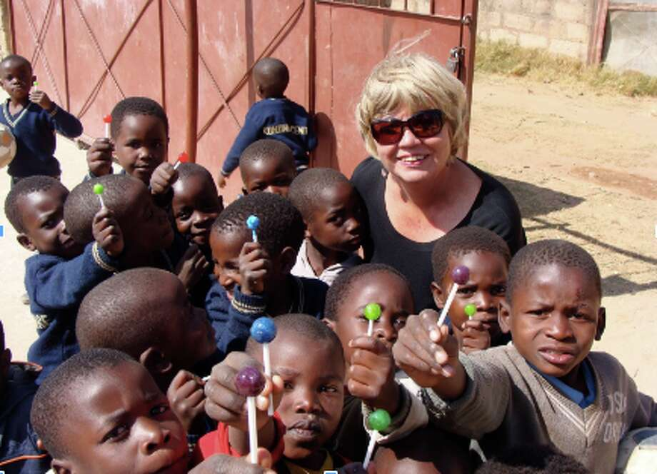Mrs. Ginger Clarke, surrounded by students of Kondwa Centre for Orphans, enjoying lollipops that were brought for them to enjoy.