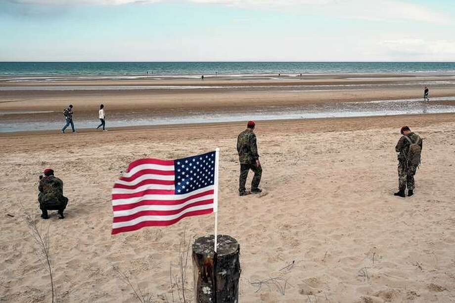 Soldiers of the Bundeswehr, the German armed forces, walk Thursday near an American flag presumably left by a visitor on Normandy's Omaha Beach on the 75th anniversary of the World War II Allied D-Day invasion. On June 6, 1944, American infantry troops stormed Omaha Beach and faced stiff German resistance, resulting in the loss of more than 1,000 American lives. Veterans, families, visitors, political leaders and military personnel gathered in Normandy to commemorate D-Day, which heralded the Allied advance toward Germany and victory about 11 months later. Photo: Sean Gallup | Getty Images