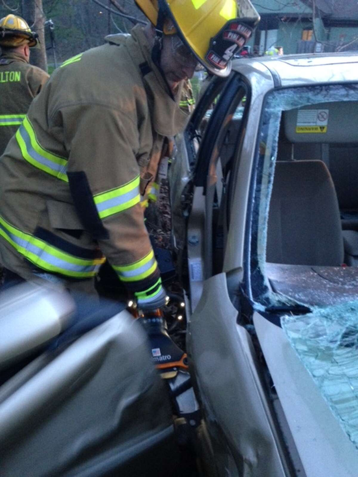 Shelton FF Cody Studwell using hydraulic spreaders to remove a car door.