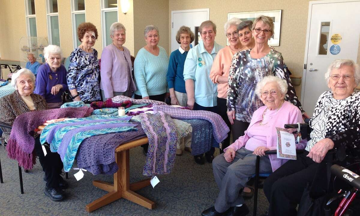 Members of the Wesley Village knitting group gather for a photo during an annual Prayer Shawl Blessing. The group of staff, residents, and volunteers knits shawls and blankets for those in need throughout the year.