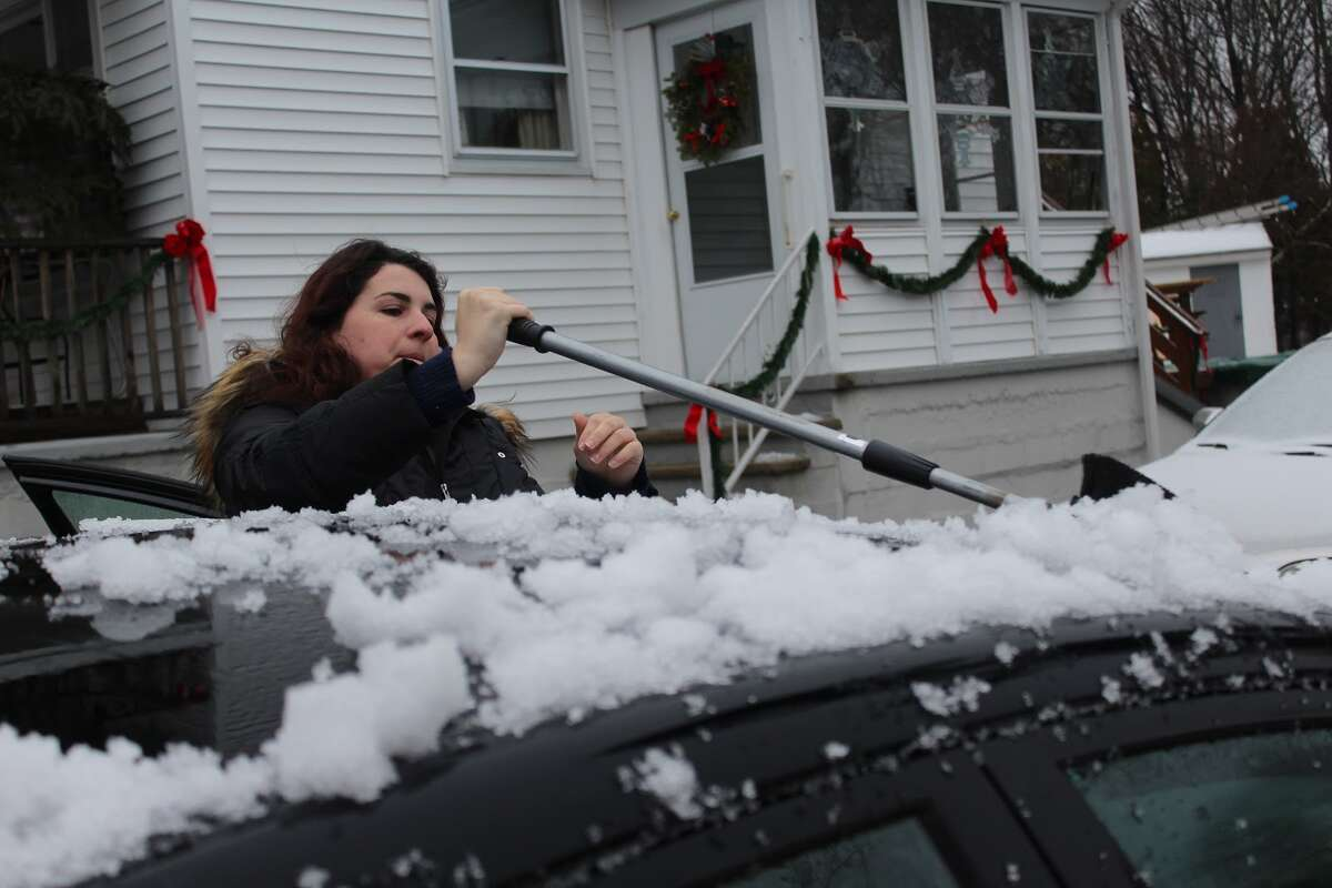 Cara Petitti cleans the first snow fall of winter 2015 off her car before heading to work - Aaron Berkowitz photo