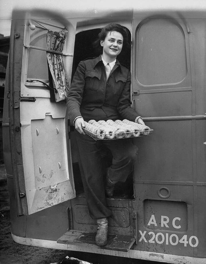 Youngest member of the Red Cross Clubmobile Katherine Spaatz, dispensing doughnuts, coffee, cigarettes and gum. (Stationed in England in WWII, 1944, according to TIME.) (Photo by Bob Landry/The LIFE Picture Collection/Getty Images) Photo: Bob Landry/The LIFE Picture Collection/Gett / Time Life Pictures