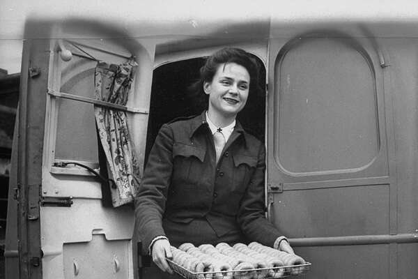 Youngest member of the Red Cross Clubmobile Katherine Spaatz, dispensing doughnuts, coffee, cigarettes and gum. (Photo by Bob Landry/The LIFE Picture Collection/Getty Images)