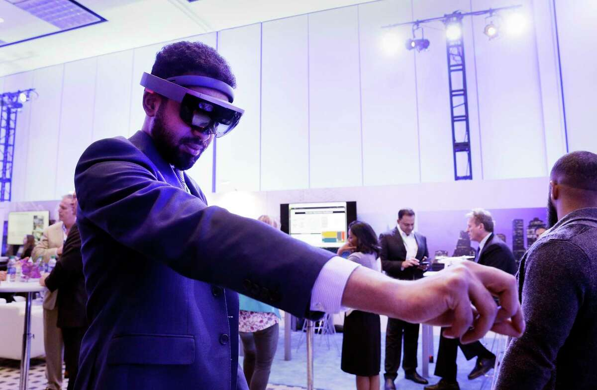 Amid moody and colorful lighting, conference attendant Almutassim Ghazali with Saudi Aramco, tries on an ABB augmented reality headset in the Microsoft room displaying various energy technologies during the second day of CERAWeek by IHS Markit at the George R. Brown Convention Center in 2019. This year's event has gone virtual, another blow to the region's convention business.