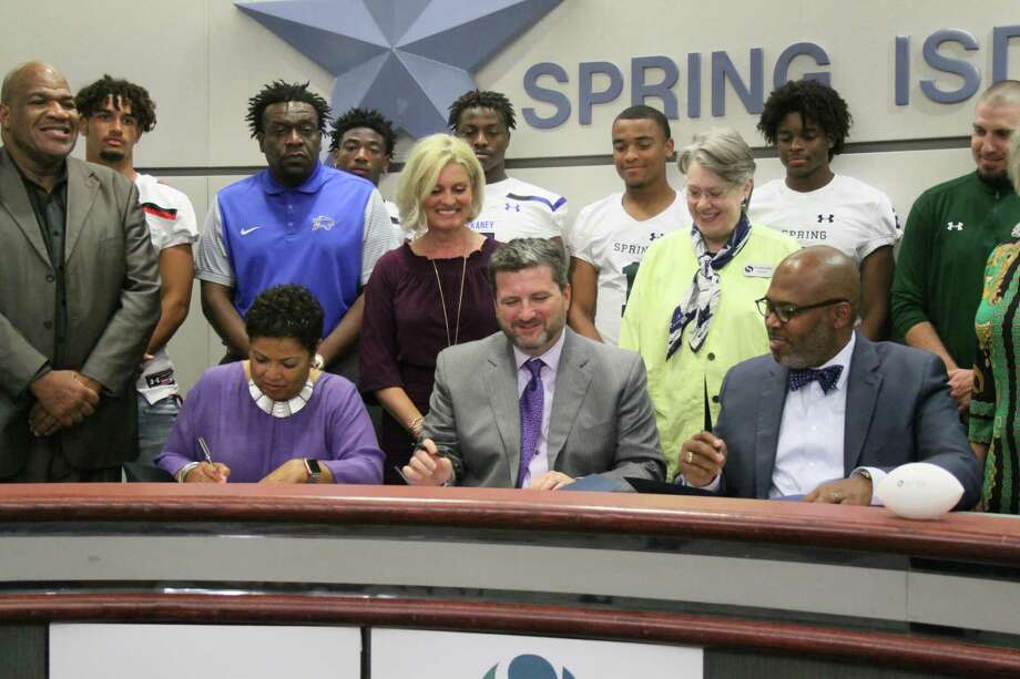 Spring ISD board president Rhonda Newhouse (bottom left) signs a deal with Planet Ford general manager Shawn Burns to name the new district's stadium, along with superintendent Rodney Watson on Thursday, June 6, 2019. Photo: Mayra Cruz
