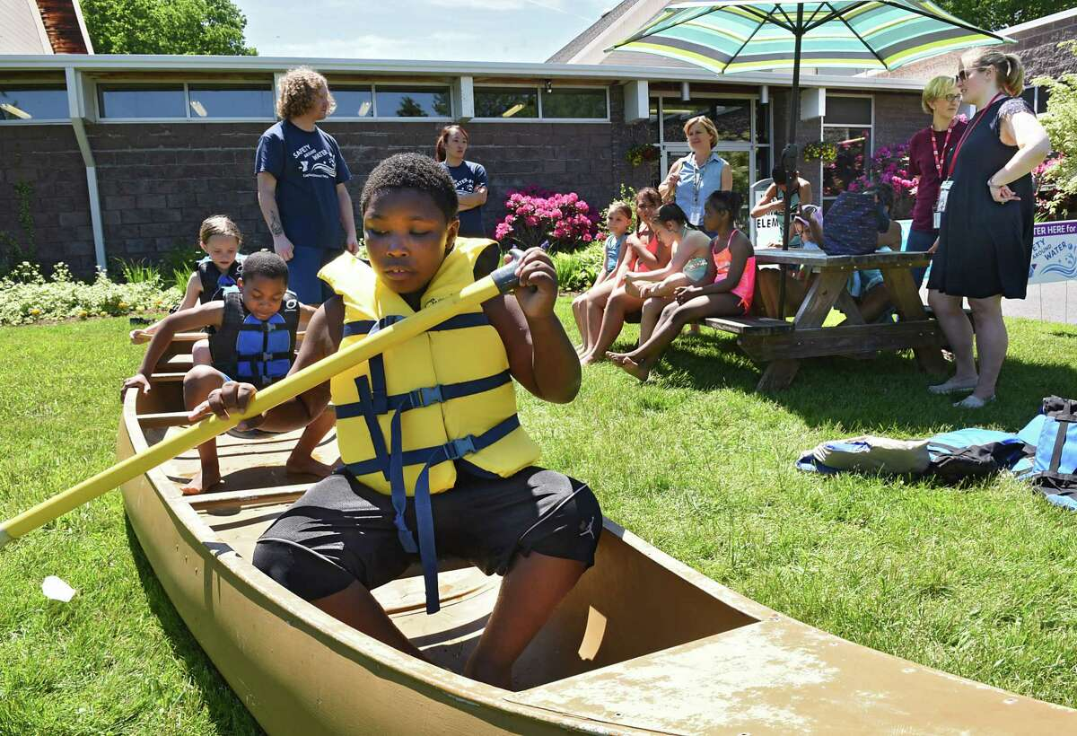 Instructor Kevin Dearaway, standing at back of canoe, teaches, left to right in boat, Abigail Rosenthal, 8, Kayden Martin, 9, and Phillip Houston, 9, boat safety during a event where YMCA staff teach children to be safe in and around water at the Glenville YMCA on Friday June 7, 2019 in Glenville, N.Y. (Lori Van Buren/Times Union)