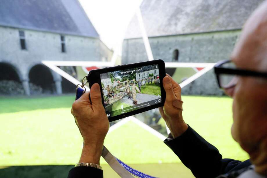 """Testing and final adjustments are made to the new """"D-Day: Freedom from Above"""" interactive augmented reality exhibit at the National Museum of the U.S. Air Force, in Dayton, Ohio, May 10, 2019. Visitors can access tablets that use a French-developed technology called HistoPad. Users can contrast current views of historic sites with detailed re-creations of them, enhanced in this case with video footage, photos and maps and animation. It will be the first use of the technology outside of France. Photo: John Minchillo / Associated Press / Copyright 2019 The Associated Press. All rights reserved."""