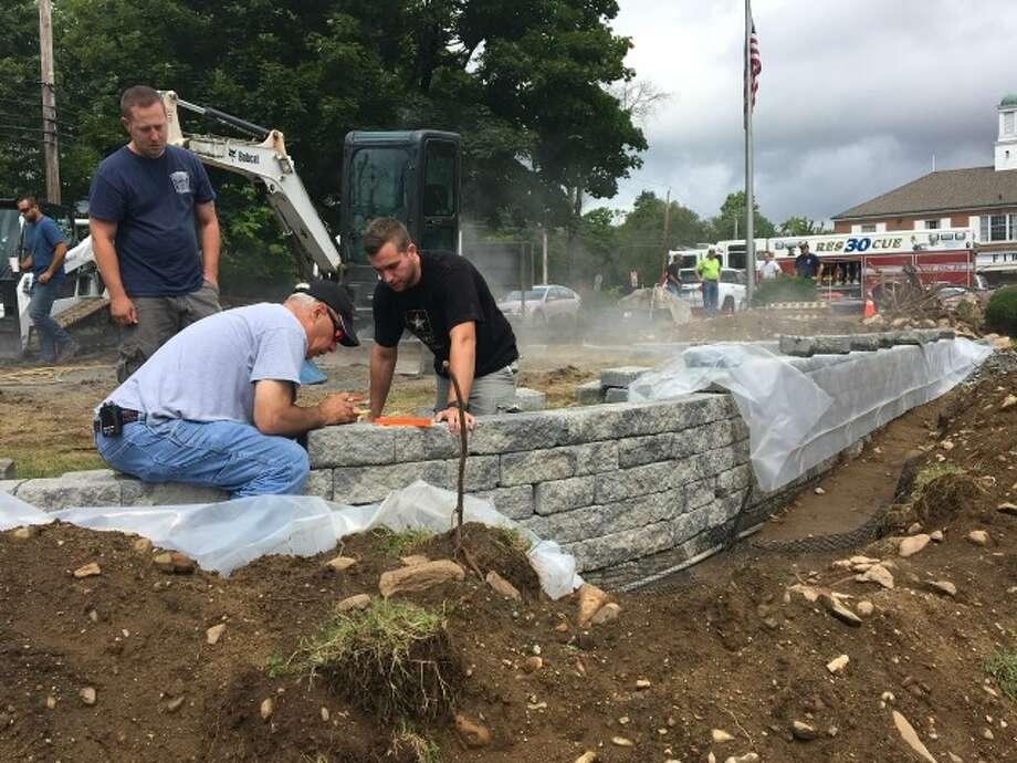 Huntington Fire Company No. 3 members Chris Waite, President Robert Araujo and Chris Patrick work Sunday on a retaining wall for the memorial. — Kate Czaplinski photos