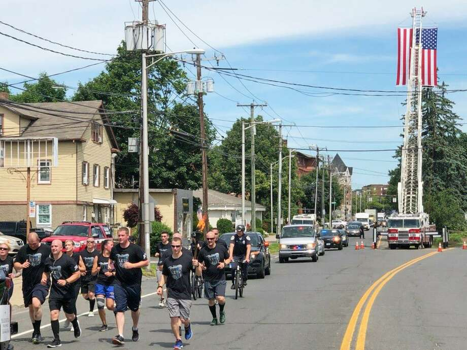 Danbury firefighters set up an aerial to display the American flag as police officers made their way from Federal Road to South Street during the Connecticut Law Enforcement Torch Run for Special Olympics on Friday, June 7, 2019. Photo: Danbury Fire Department / Facebook