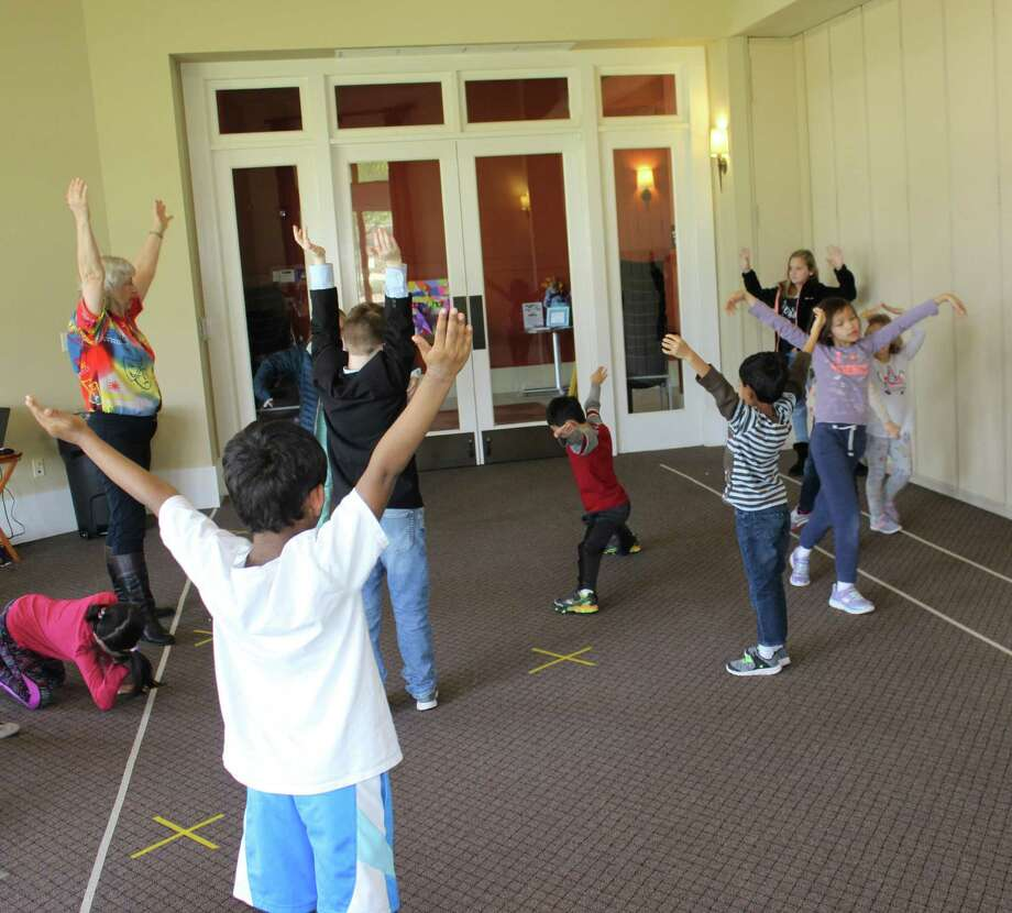 Ann Marie Morris, director/teacher, Drama Kids Katy, Houston & Fulshear, leads a spring break class in a routine called Bright Balloon. Students without saying a word move an imaginary balloon to music. Morris also is co-owner of the franchise. Photo: Drama Kids / Drama Kids