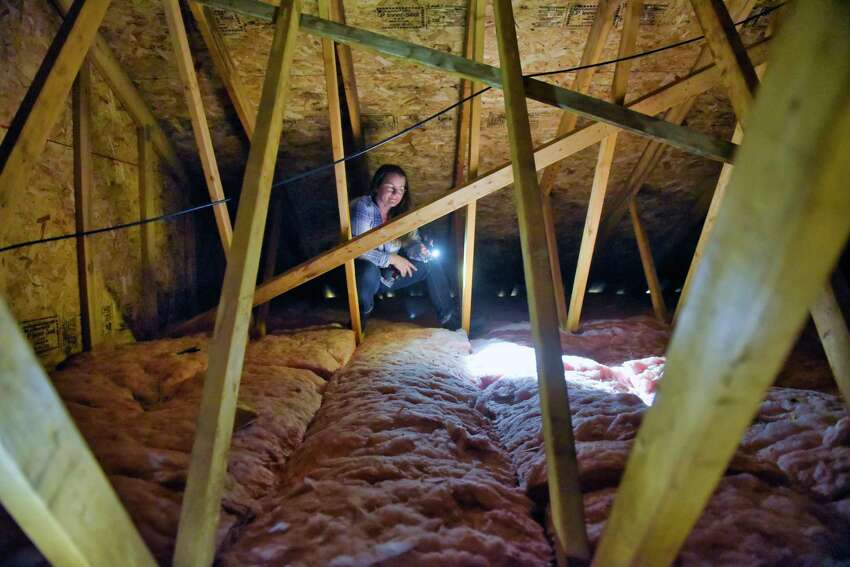 Home inspector Jolene Lomnes, owner of Informative Home Inspections, checks out the attic at a home on Wednesday, May 8, 2019, in the Town of Ballston, N.Y. (Paul Buckowski/Times Union)