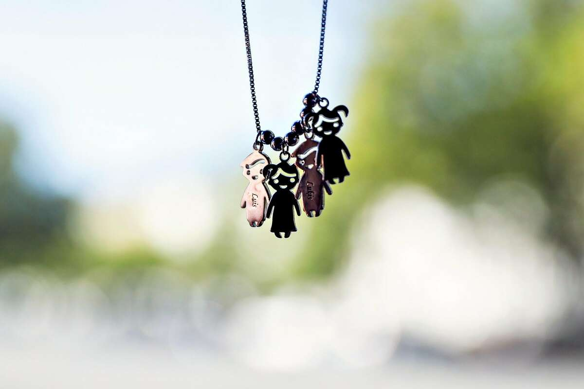 Annette Rivero's (not pictured) necklace with figures of her children hang from her rear view mirror as she drives Lyft in San Jose, California, on Tuesday, June 4, 2019. She was given the necklace for Mother's Day.