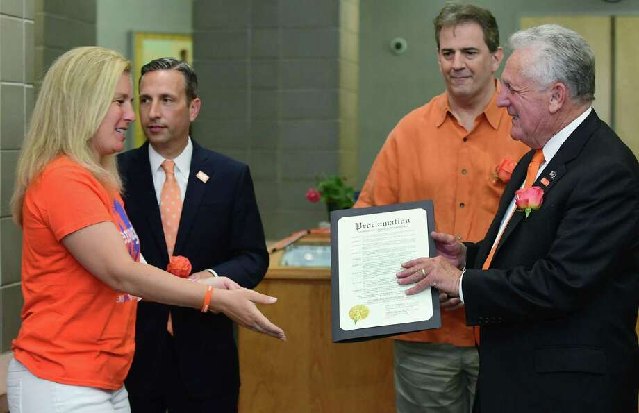 Members of Moms Demand Action, a nonprofit aimed at addressing gun violence, including co-lead Jennifer Balliett recive a proclamation from Norwalk Mayor Harry Rilling as State Senate Majority leader Bob Duff and State Representative Chris Perone lookk on Friday, June 7, 2019, as a part of a #WearOrange event to commemorate gun violence prevention week and honor the victims of gun violence at Norwalk City Hall in Norwalk, Conn. Photo: Erik Trautmann / Hearst Connecticut Media / Norwalk Hour