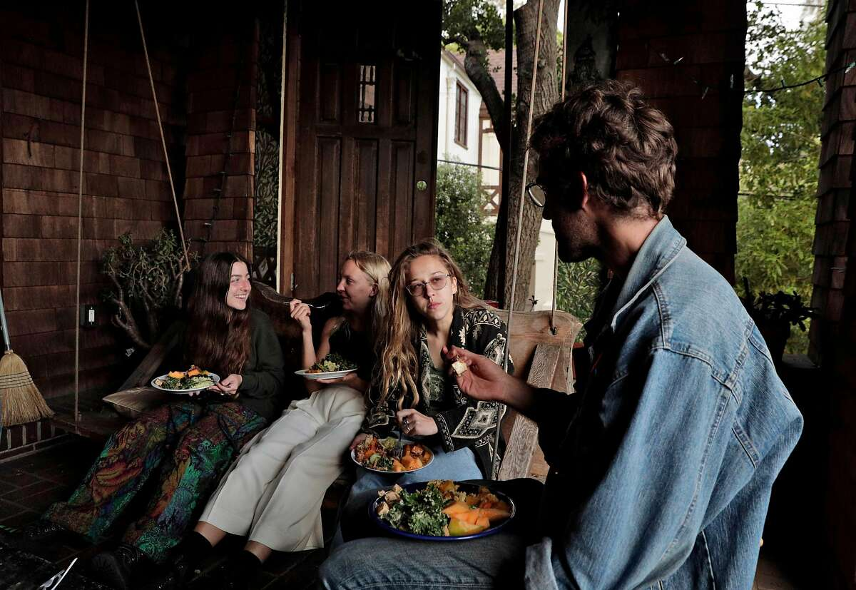 Housemates (l-r) Paige Rosenberg, Margot Schumacher, Izzi Niewiadomski, and Keaton Peters enjoy dinner on the porch at the cooperative house known by members as Lothlorien, in Berkeley, Calif., on Tuesday, May 7, 2019. Berkeley's unique co-ops, formed decades ago to give low-income university students a place to live, are turning more affluent and less diverse.