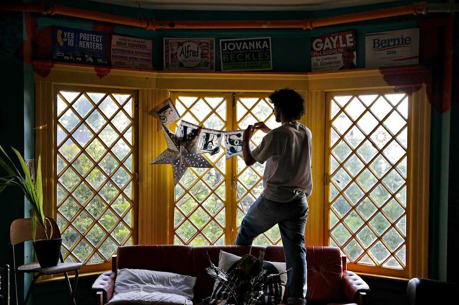 Giancarlo Tucci-Berube replaces a decoration in the window at Loth. Photo: Carlos Avila Gonzalez / The Chronicle