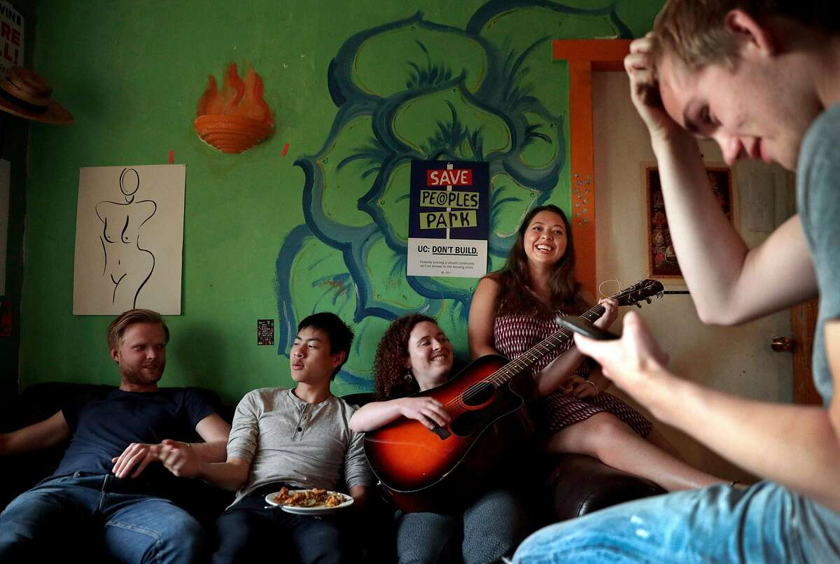 Housemates (l-r) Jonathan Mortenlind, Alex Ye, Daryanna Lancet, Ella Smith, and Niklas Peters spend time in the living room after dinner at the cooperative house known by members as Lothlorien, in Berkeley, Calif., on Tuesday, May 7, 2019. Berkeley's unique co-ops, formed decades ago to give low-income university students a place to live, are turning more affluent and less diverse.