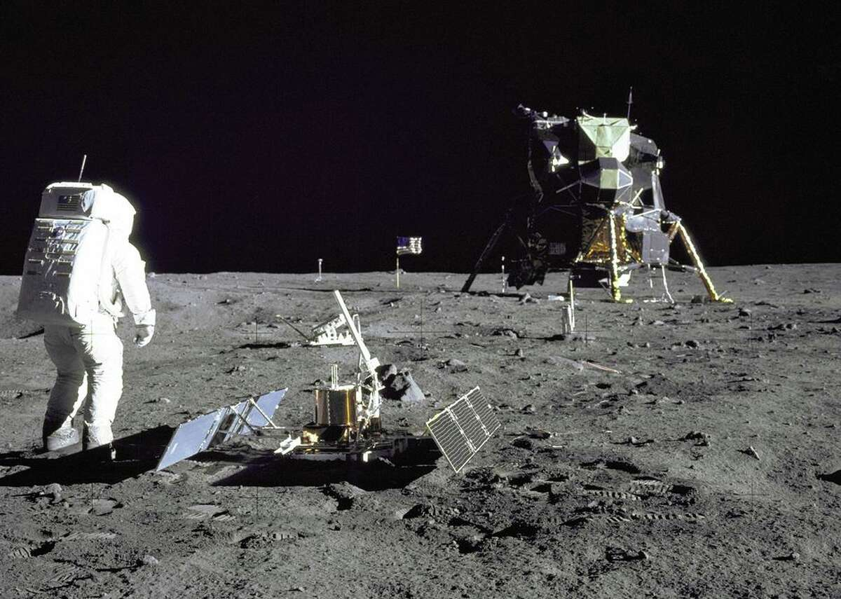 Buzz Aldrin stands on the moon beside seismic measurement gear, part of the Early Apollo Scientific Experiments Package. To the right is the lunar module Eagle.