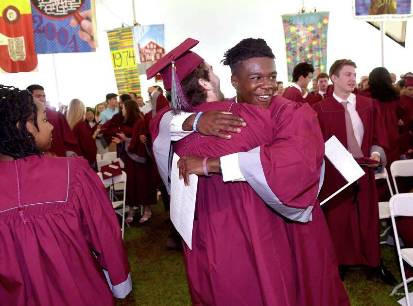 Hopkins School graduates Tyler Cipriano (center with back to camera) and Douglas Guilford (center) celebrate at the completion of commencement in New Haven on June 7, 2019.