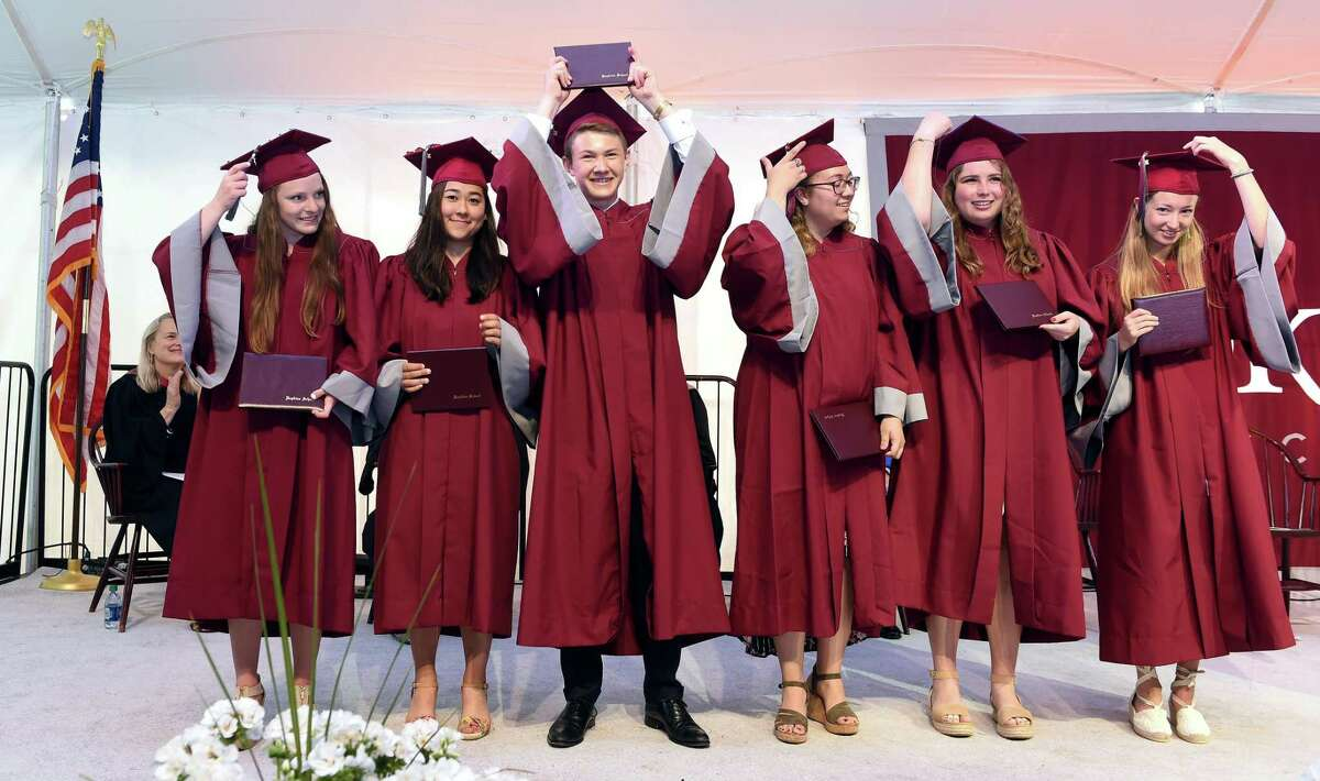 Hopkins School graduate Benjamin Levine (center) holds his diploma up high during commencement in New Haven on June 7, 2019.