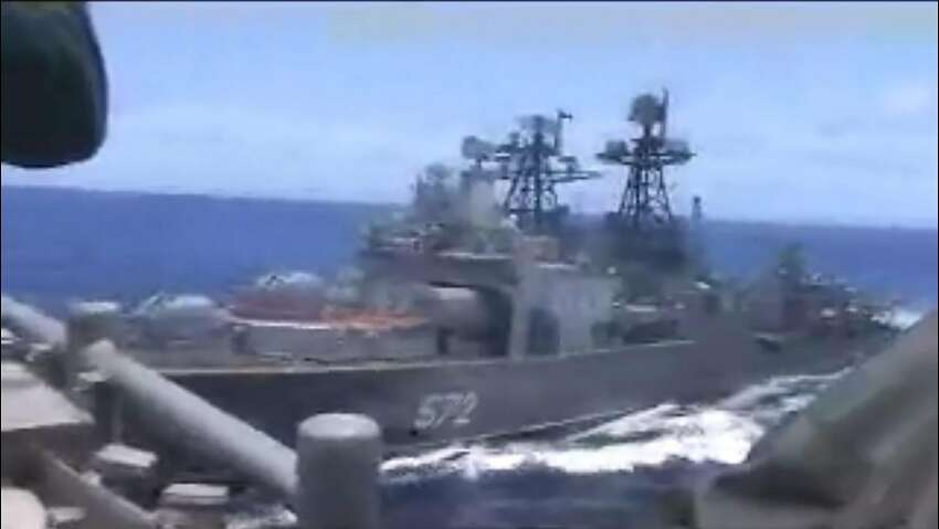 The Russian destroyer (572) sails close to the American guided-missile cruiser Chancellorsville in the Philippine Sea.
