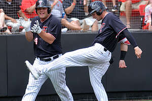 Texas Tech players Tanner O'Tremba (left) and Gabe Holt celebrate after scoring on a hit by Brian Klein to take a 5-0 lead over Army in the second inning of their Lubbock Regional baseball game on Friday at Rip Griffin Park in Lubbock. The host Red Raiders rolled to an 11-2 win to open up region play.