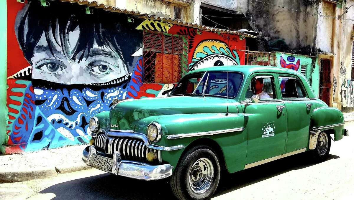 """A driver of an """"almendron,"""" as old Cuban cars serving as private taxis are locally called, passes by graffiti art in Old Havana on May 25, 2019."""