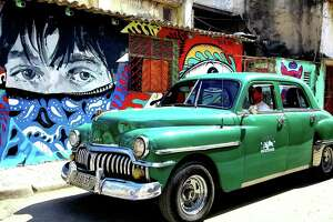"A driver of an ""almendron,"" as old Cuban cars serving as private taxis are locally called, passes by graffiti art in Old Havana on May 25, 2019."