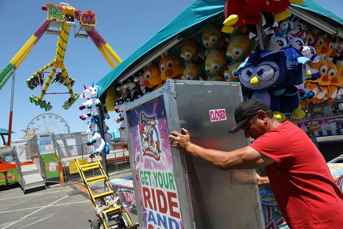 Gabriel Moreno, IT Butler Amusements, moves a ticket machine into position in the carnival section during a media preview of the San Mateo County Fair at the San Mateo Events Center on Friday, June 7, 2019 in San Mateo, Calif.