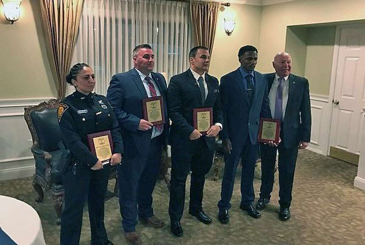 Mark Pappas, Arlindo Dos Santos, Diala Roberts and Thomas Flaherty -- all Bridgeport, Conn., police officers -- stand with Police Chief Armando Perez at a ceremony after the four officers each received a Meritorious Service Award.
