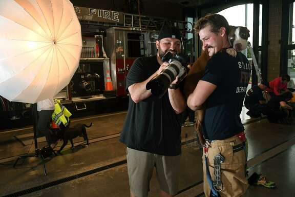 """Robert Harrington, left. of Bella Media, shares a photograph with firefighter Forrest McCord who was being photographed with """"Edan"""", 1, from the Harris County Animal Shelter, for the Spring Fire Dept.'s first calendar at Station 75 in Spring on June 6, 2019."""