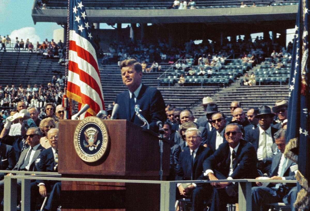 """On Sept. 12, 1962, President John F. Kennedy tells a crowd of 35,000 at Rice University Stadium in Houston, Texas, """"We choose to go to the Moon in this decade and do the other things, not because they are easy, but because they are hard, because that goal will serve to organize and measure the best of our energies and skills, because that challenge is one that we are willing to accept, one we are unwilling to postpone, and one in which we intend to win, and the others, too."""""""